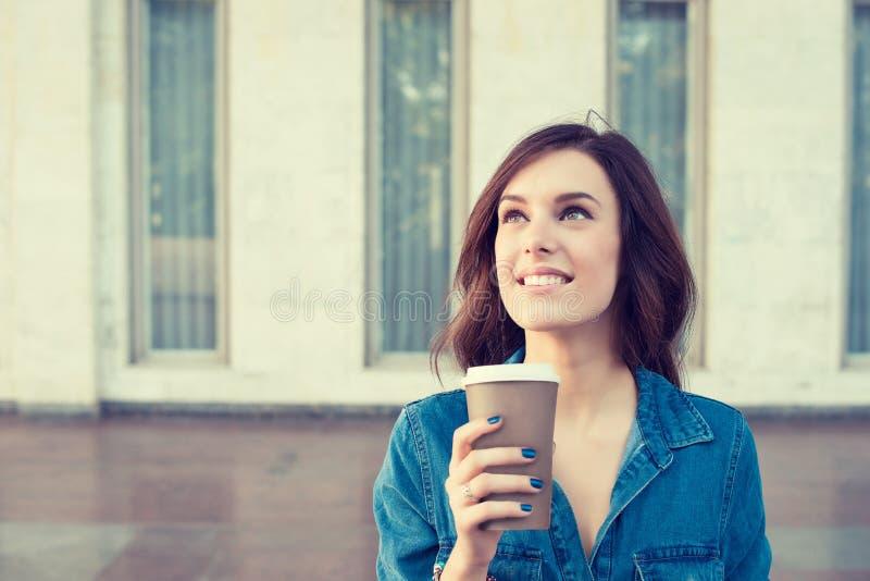 Café potable de femme tenant dehors la tasse de papier photographie stock