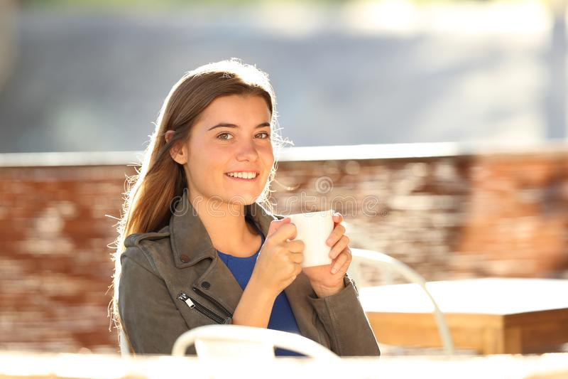 Café potable de fille et regarder l'appareil-photo dans une barre photos stock
