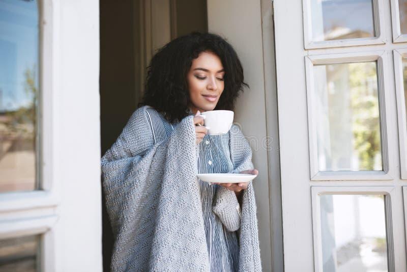 Café potable de gentille fille d'Afro-américain dans le restaurant Jeune fille se tenant avec la tasse de café et rêveusement fer photos stock