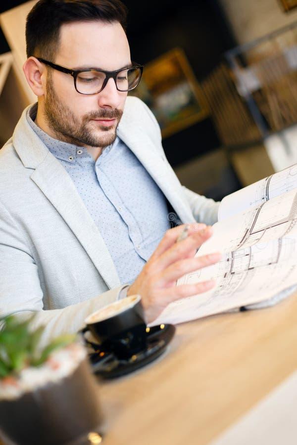Café potable de jeune architecte tout en regardant au-dessus des plans de bâtiment dans un café moderne photographie stock