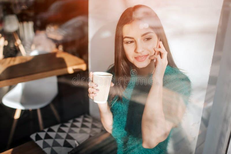 Café potable de jeune belle femme à la barre de café Young modèle féminin à l'aide du smartphone au café photos stock