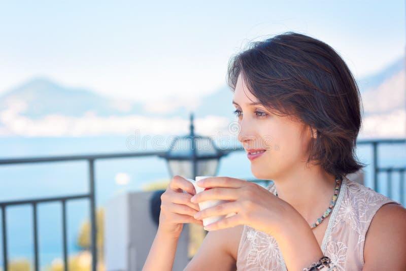 Café potable de jeune femme à la terrasse de café photos stock