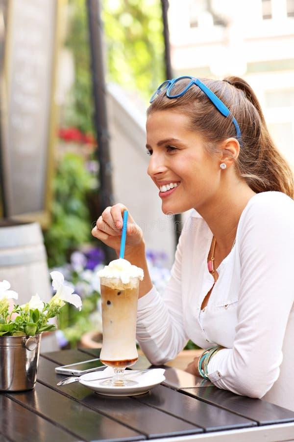 Café potable de jeune femme dans un café photo stock