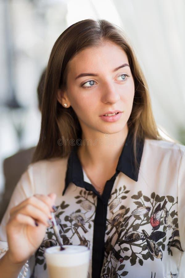 Café potable de jeune femme de beauté dans un café extérieur photo libre de droits