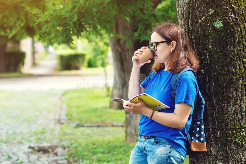 Café potable de jeune femme et lecture d'un livre au parc d'été La fille d'étudiant apprécie la récréation extérieure Étudiante t image libre de droits