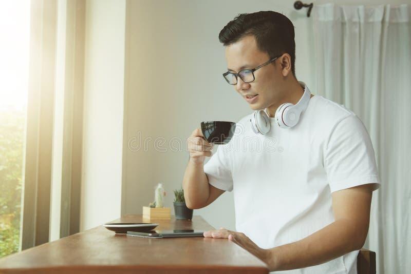 Café potable de jeune homme asiatique et à l'aide du comprimé numérique dans le coff images libres de droits