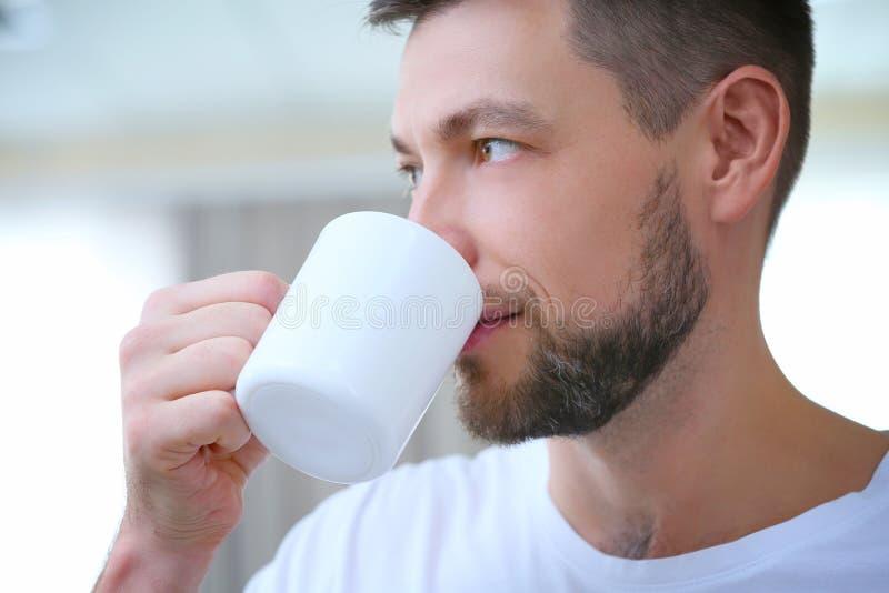 Café potable de jeune homme beau à la maison, photos stock