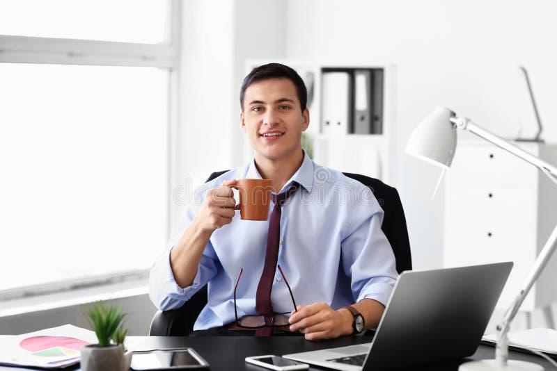 Café potable de jeune homme d'affaires beau dans le bureau image libre de droits