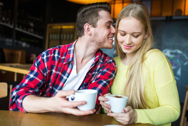 Café potable de jeune homme et de femme dans un restaurant Café potable de jeune homme et de femme une date Homme et femme une da photos libres de droits