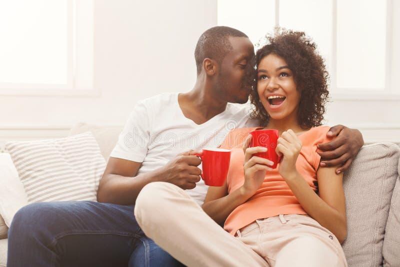 Café potable de sourire de couples noirs à la maison photo stock