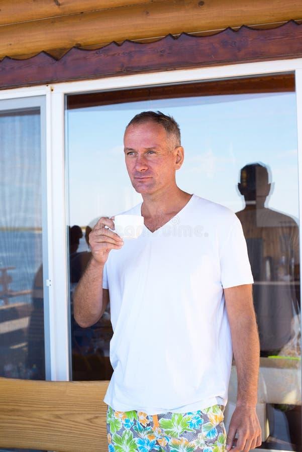 Café potable de sourire d'homme sur la côte photographie stock libre de droits
