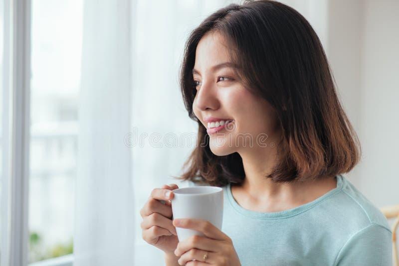 Café potable de sourire de femme asiatique détendant sur le divan au hom images libres de droits