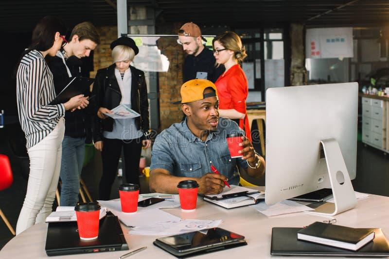 Café potable de sourire de jeune homme africain tout en se reposant à la table et à l'aide de l'ordinateur dans le bureau moderne image libre de droits