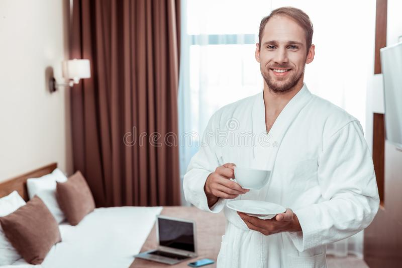 Café potable de sourire de matin d'homme aux cheveux courts tout en portant photo stock