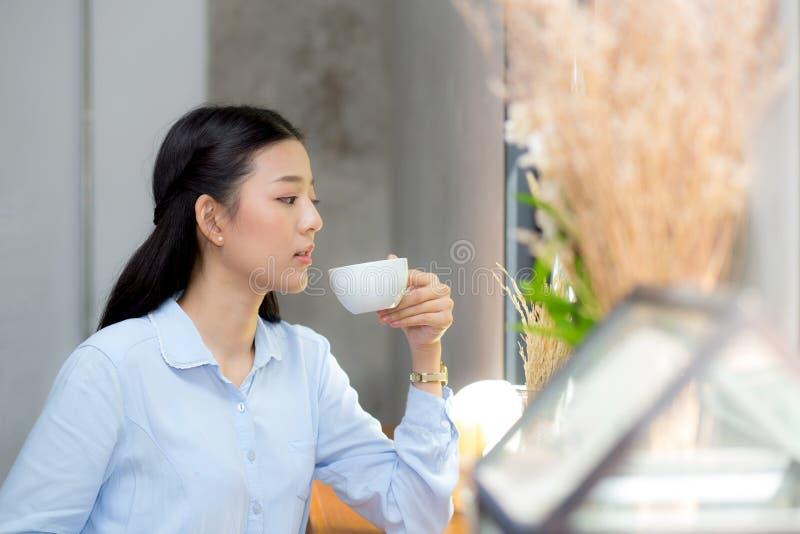 Café potable et sourire de belle jeune femme asiatique pendant le matin au café, fille s'asseyant dans le café images stock
