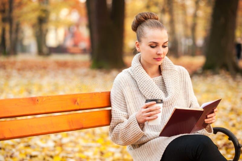 Café potable femelle assez caucasien et lecture photographie stock libre de droits