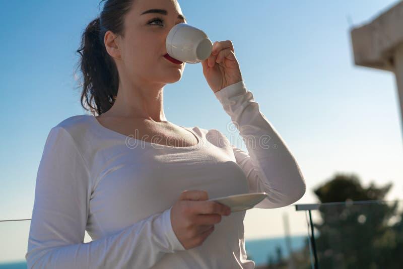 Café potable ou thé de femme attirante sur le balcon avec le beau panorama photographie stock libre de droits
