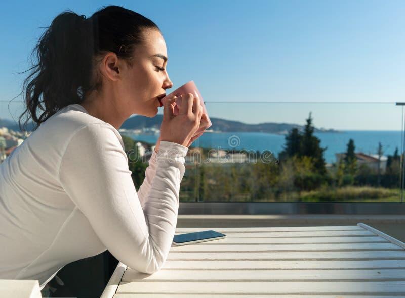 Café potable ou thé de jolie femme sur le balcon avec le beau panorama de paysage photographie stock libre de droits