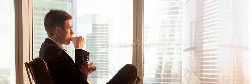 Café potable se reposant d'homme d'affaires détendu par vue horizontale regardant la fenêtre photos libres de droits
