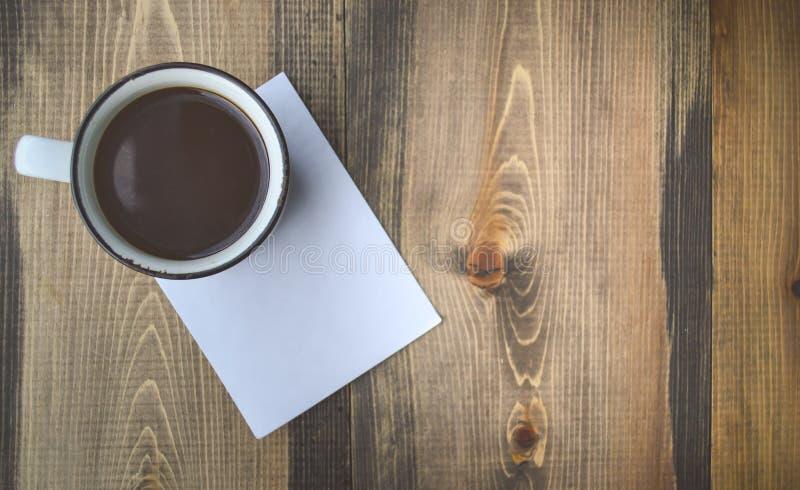 Café preto e bloco de notas no fundo de madeira no tom do vintage imagem de stock royalty free
