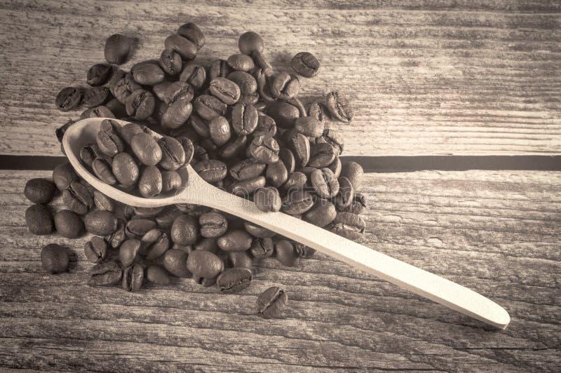 Café preto e colher de madeira com os grãos de café no fundo de madeira do vintage imagens de stock
