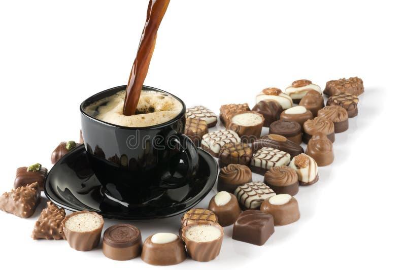 Café preto e doces de derramamento. imagem de stock