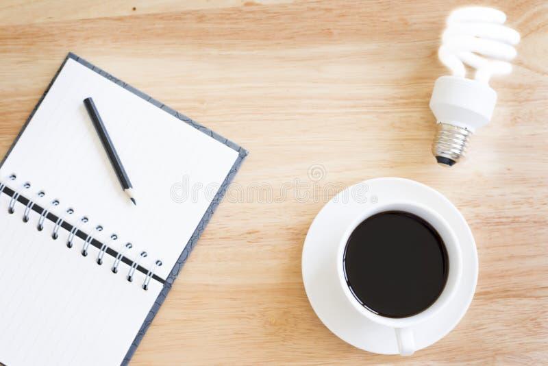 Café preto na tabela de madeira E ilumine a lâmpada imagem de stock royalty free