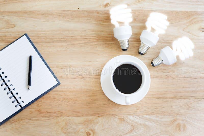 Café preto na tabela de madeira E ilumine a lâmpada imagem de stock