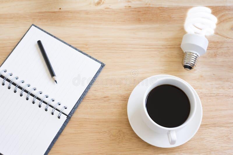 Café preto na tabela de madeira E ilumine a lâmpada fotografia de stock