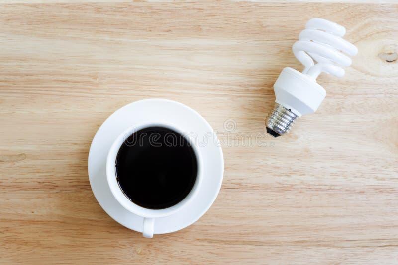 Café preto na tabela de madeira E lâmpada imagens de stock