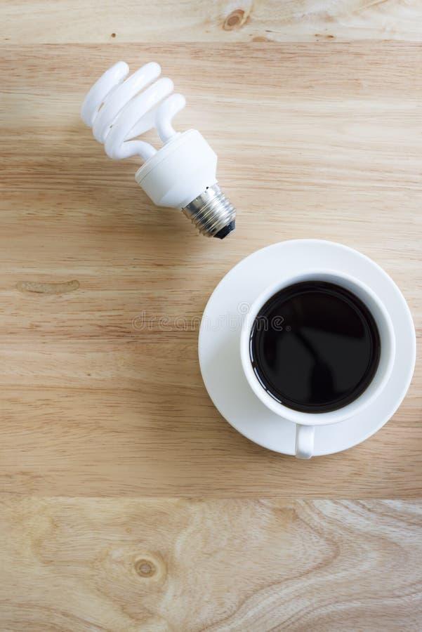 Café preto na tabela de madeira E lâmpada foto de stock royalty free