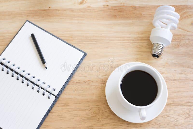 Café preto na tabela de madeira E lâmpada fotografia de stock