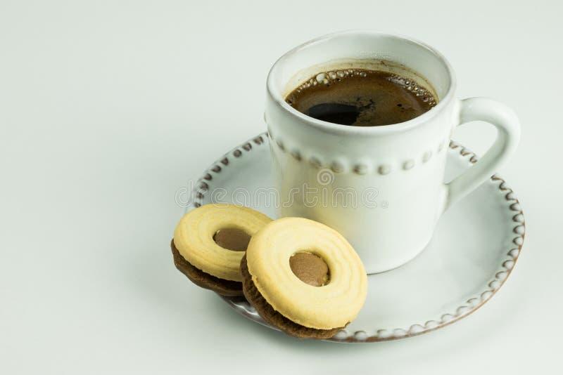 Café preto no copo branco com as cookies dos pires e do twoo, na placa de tabela branca como o fundo foto de stock royalty free