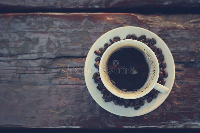 Café preto no copo na tabela de madeira velha, vista superior imagem de stock