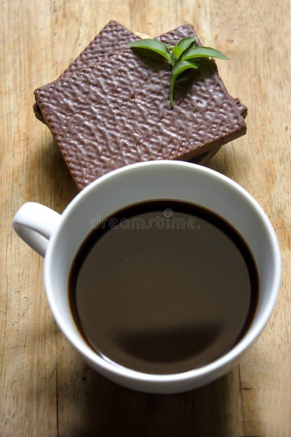 Café preto no vidro e no chocolate brancos da bolacha imagens de stock royalty free