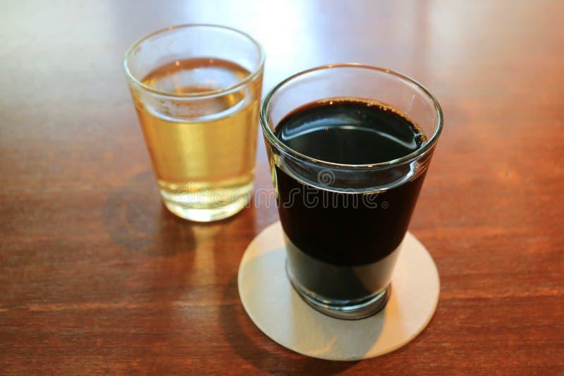 Café preto quente e chá chinês quente nos vidros transparentes servidos na tabela de madeira imagem de stock