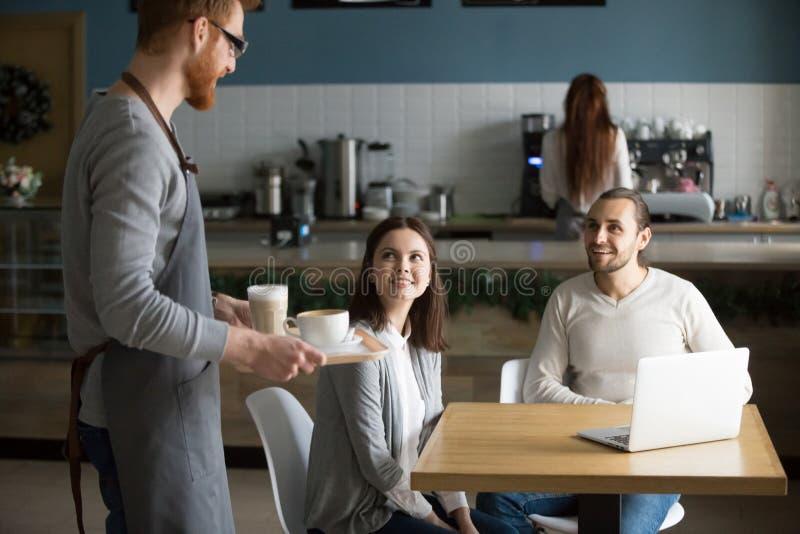 Café que lleva del camarero a los pares sonrientes que esperan en la tabla del café imagen de archivo