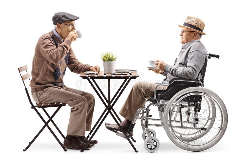 Café que se sienta y de consumición del hombre mayor con un hombre discapacitado en una silla de ruedas imagenes de archivo
