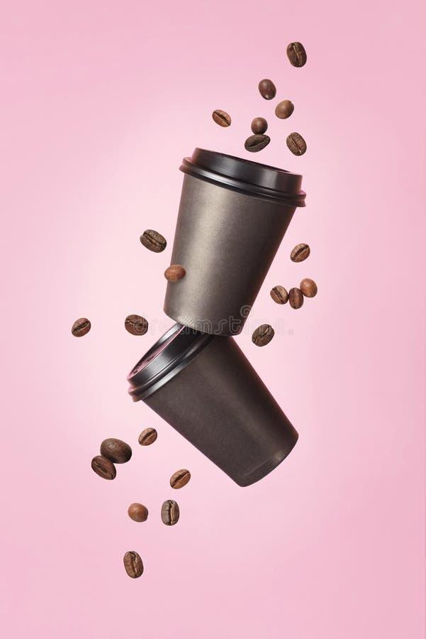 Café que vuela de tazas de papel con los granos de café del vuelo en un fondo rosado Concepto del café Mofa para arriba Café vací fotos de archivo