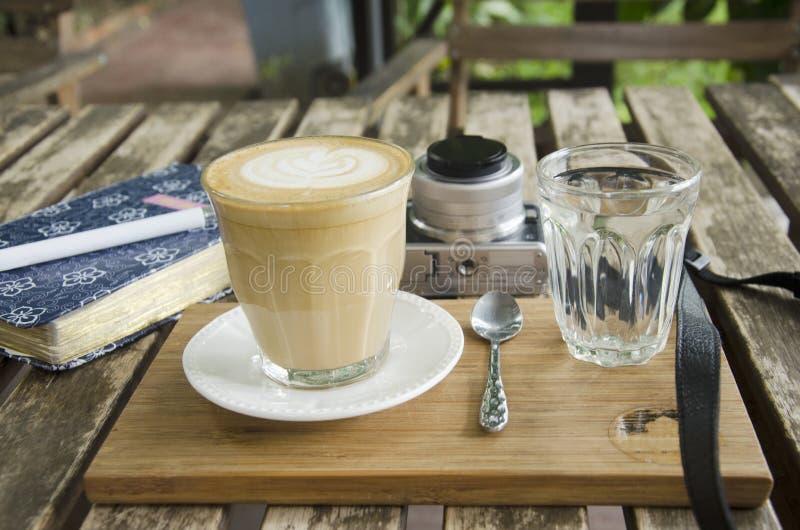 Café quente da arte do Latte com livro de nota e câmera do blogger dos viajantes imagem de stock royalty free