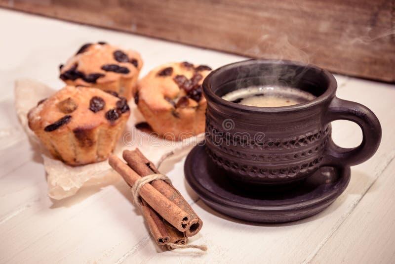 Café quente da manhã, varas de canela e três queques no fundo de madeira imagens de stock