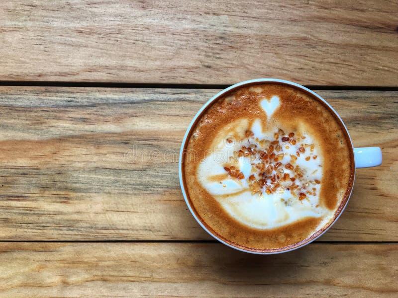 Café quente do cappuccino no copo branco com o açúcar de bastão marrom que cobre no fundo de madeira da tabela foto de stock