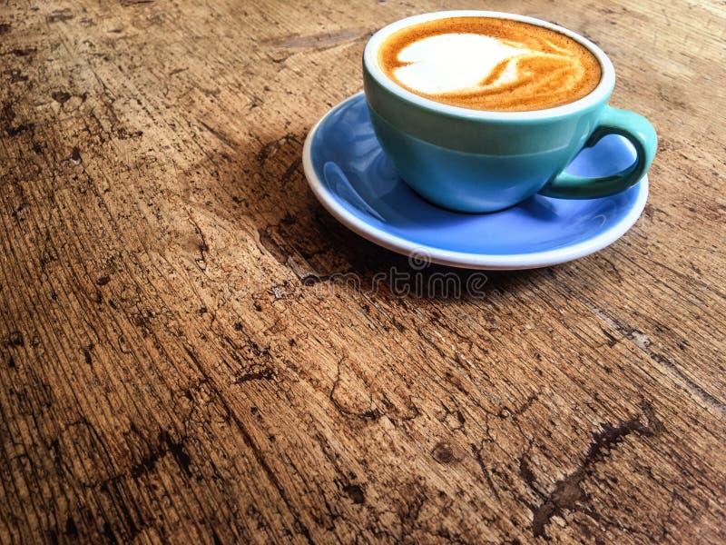 Café quente do Latte da arte em um copo na cafetaria na sagacidade de madeira da tabela fotos de stock