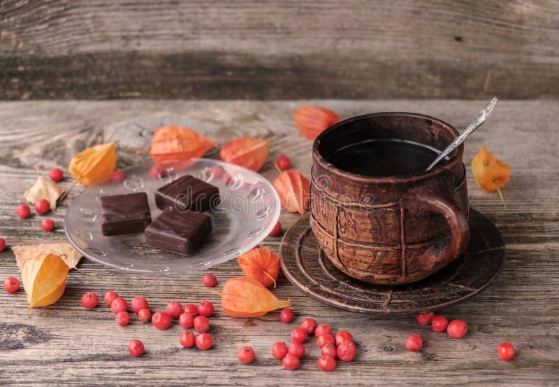 Café quente em uma caneca cerâmica e em chocolates imagens de stock royalty free