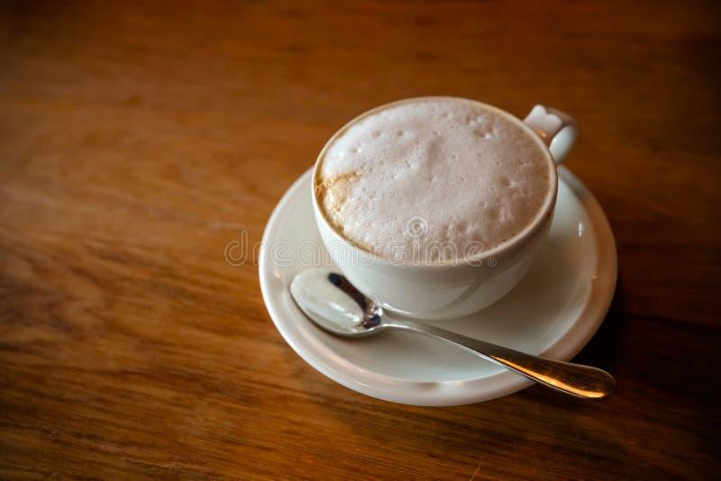 Café quente fresco pela vista superior na tabela de madeira café do cappuchino no copo e nos pires porcellan brancos com colher d foto de stock royalty free