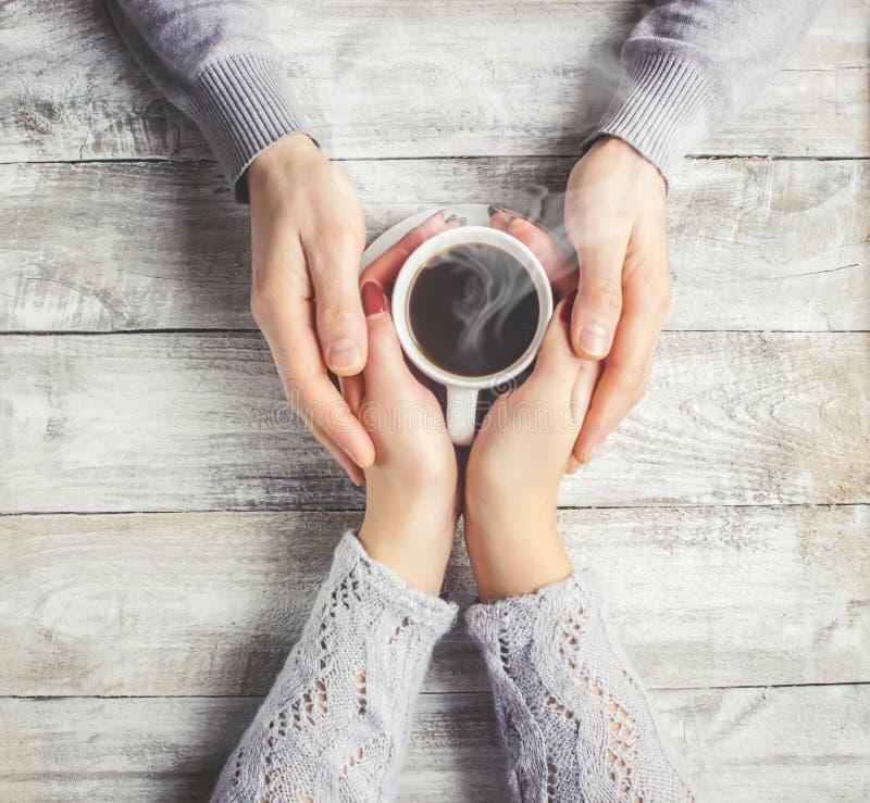 Café quente nas mãos de uma amada imagens de stock royalty free