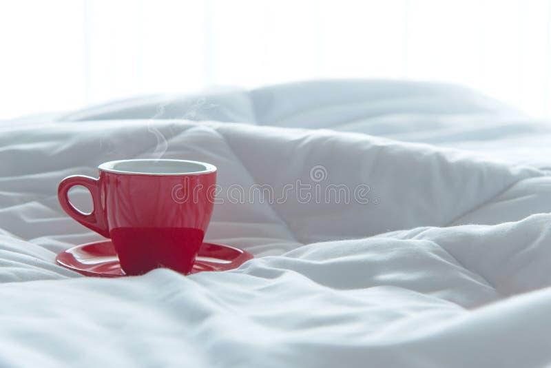 Caf? rojo de la taza de la ma?ana fresca en la cama blanca foto de archivo libre de regalías