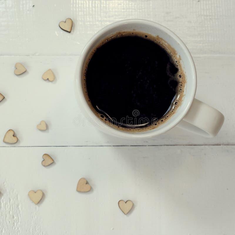 Café sólo caliente con las burbujas en el top en la taza blanca en la tabla blanca adornada con el mini corazón, concepto del amo foto de archivo