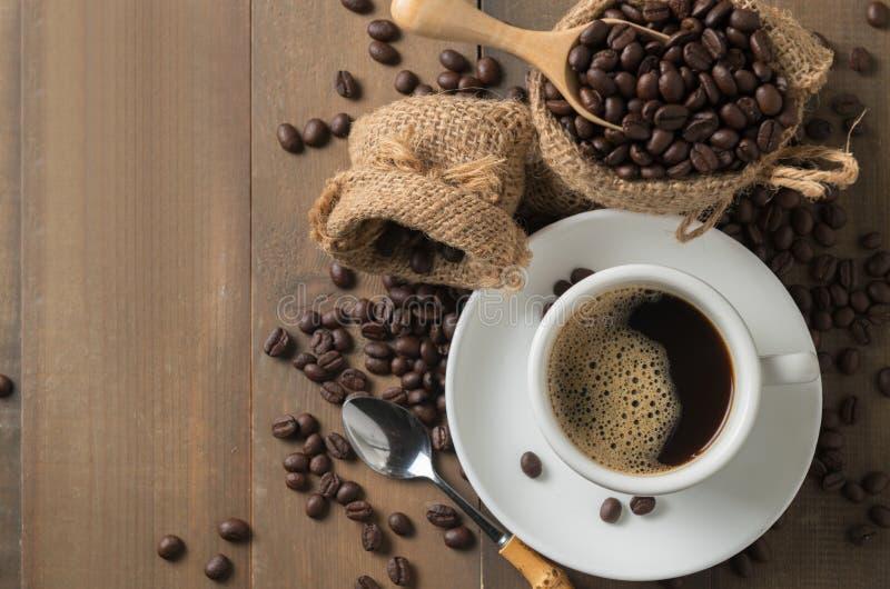 Café sólo caliente en la taza y los granos de café asados en la cucharada de madera o foto de archivo libre de regalías