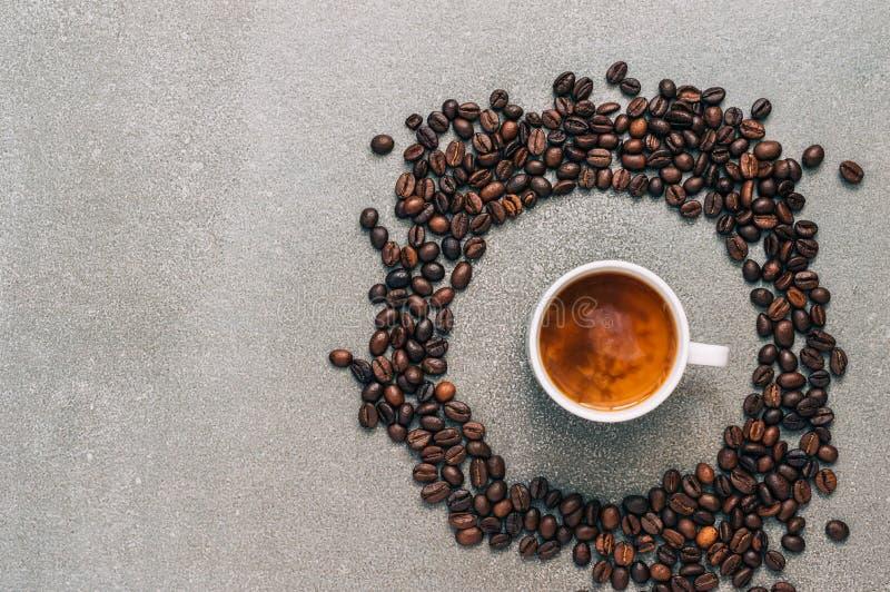 Café sólo con crema en un fondo gris rodeado por los granos de café, visión superior imagen de archivo libre de regalías
